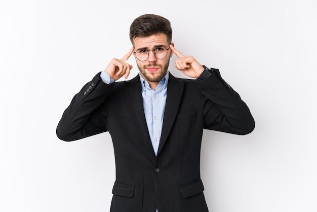 Il giovane uomo caucasico di affari si è concentrato su un compito, mantenendo l'indice che indica la testa.