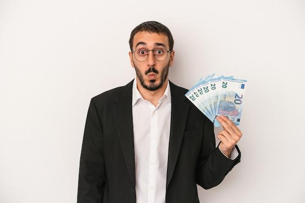 Il giovane uomo caucasico di affari che tiene le banconote isolate su fondo bianco alza le spalle e apre gli occhi confusi.