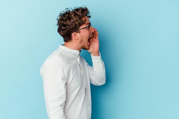 Giovane uomo d'affari caucasico isolato sulla parete blu che grida e che tiene il palmo vicino alla bocca aperta