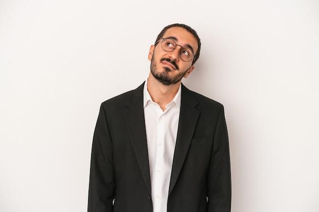 Giovane uomo d'affari caucasico isolato su sfondo bianco che sogna di raggiungere obiettivi e scopi