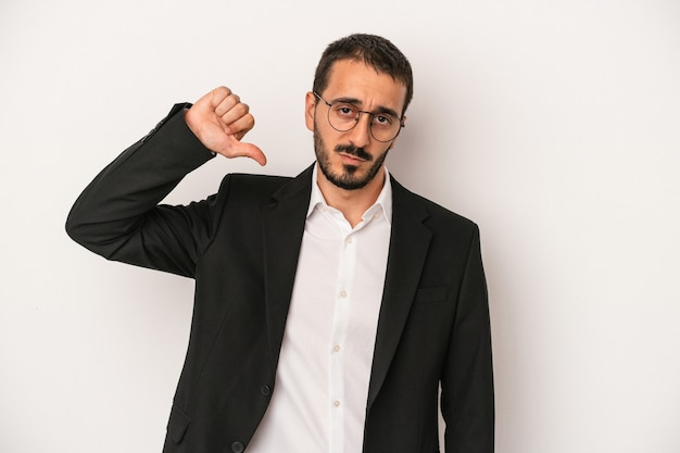 Giovane uomo d'affari caucasico isolato su sfondo bianco che mostra un gesto di antipatia, pollice in giù. concetto di disaccordo.