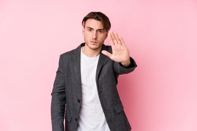 Giovane uomo d'affari caucasico in posa isolato in piedi con la mano tesa che mostra il segnale di stop, impedendoti.
