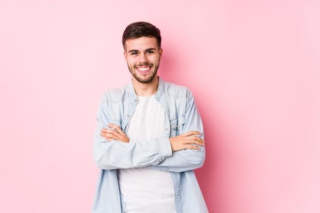 Giovane uomo d'affari caucasico in posa in un bianco isolato che si sente sicuro, incrociando le braccia con determinazione