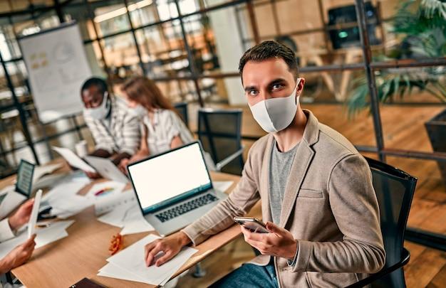 Un giovane uomo d'affari caucasico in una maschera protettiva si siede davanti a un laptop, tiene uno smartphone in mano e lavora con il suo team o con i colleghi in un ufficio in quarantena.