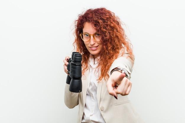 Giovane donna caucasica di affari di redhead che tiene sorrisi allegri di un binocolo che indicano la parte anteriore.