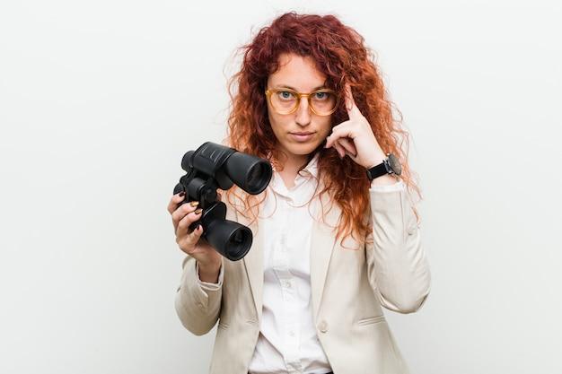 La giovane donna caucasica di affari di redhead che tiene un binocolo che indica il suo tempiale con la barretta, pensando, si è concentrata su un compito.