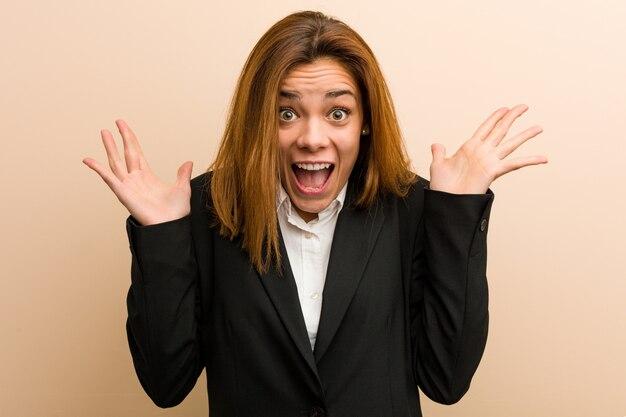 Giovane donna caucasica di affari che celebra una vittoria o un successo