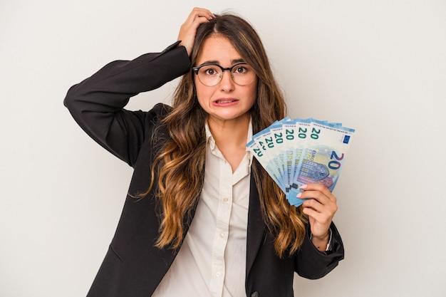 Giovane donna d'affari caucasica con banconote isolate su sfondo bianco scioccata, ha ricordato un incontro importante.