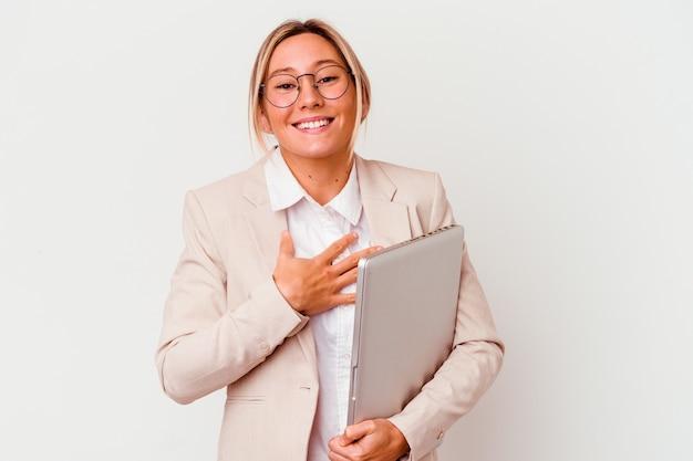 La giovane donna caucasica di affari che tiene un computer portatile isolato sul muro bianco ride ad alta voce mantenendo la mano sul petto.