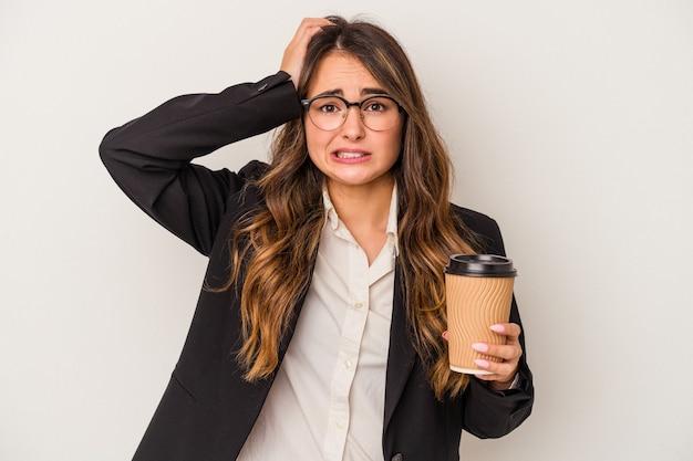 Giovane donna d'affari caucasica in possesso di un caffè da asporto isolato su sfondo bianco scioccata, ha ricordato un incontro importante.