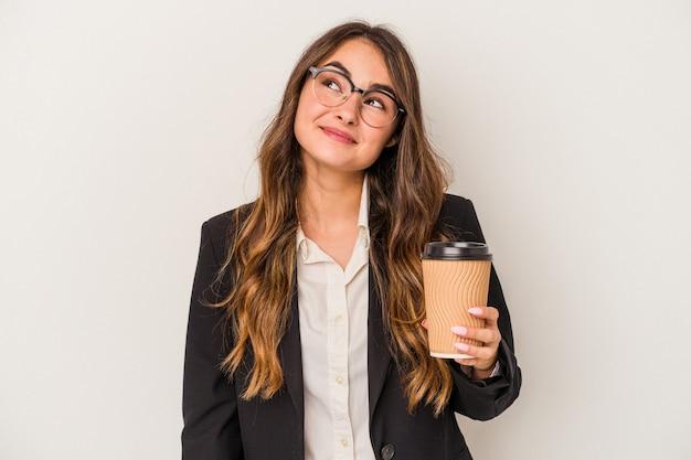 Giovane donna d'affari caucasica in possesso di un caffè da asporto isolato su sfondo bianco sognando di raggiungere obiettivi e scopi