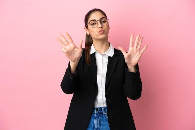 Giovane donna d'affari caucasica isolata su sfondo rosa contando nove con le dita