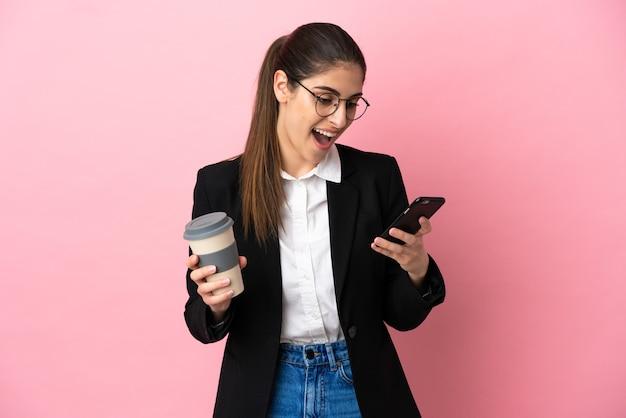 Giovane donna d'affari caucasica isolata su sfondo rosa che tiene caffè da portare via e un cellulare