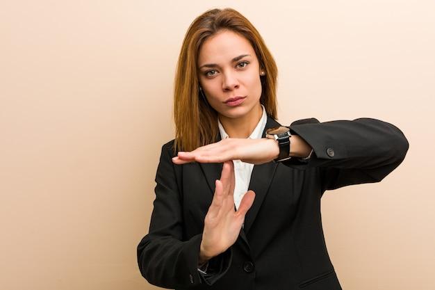 Giovane donna caucasica di affari che mostra un gesto di timeout.