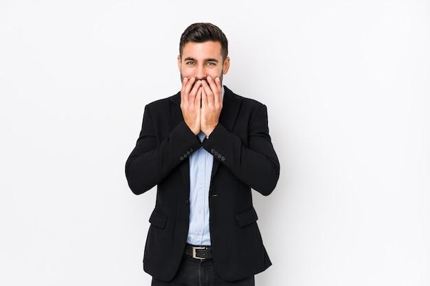 Giovane uomo d'affari caucasico contro un muro bianco isolato ridendo di qualcosa, coprendo la bocca con le mani.