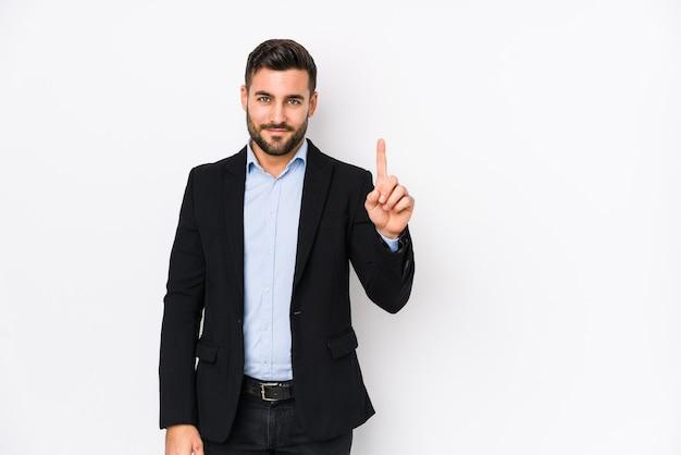 Giovane uomo d'affari caucasico contro un muro bianco isolato che mostra il numero uno con il dito.