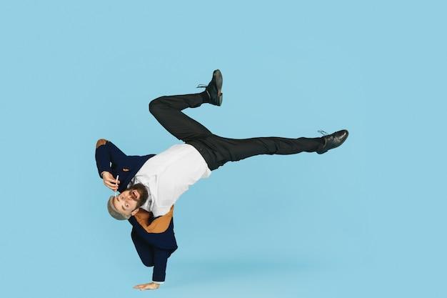 Giovane uomo d'affari caucasico che si diverte a ballare break dance su sfondo blu studio