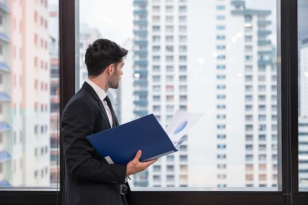 Giovane uomo d'affari caucasico che tiene documento finanziario e guardando attraverso la finestra in ufficio moderno al quartiere degli affari