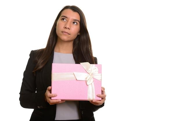 Giovane imprenditrice caucasica azienda confezione regalo pensando isolato su bianco