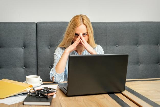 Giovane imprenditrice caucasica stanca dal lavoro seduto al tavolo in un caffè