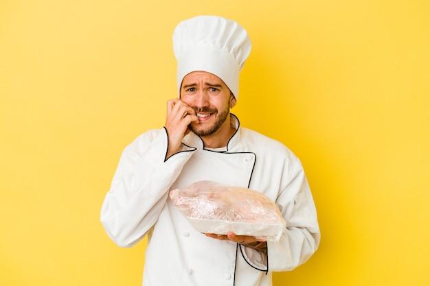 Pollo della holding dell'uomo giovane chef caucasico isolato su sfondo giallo unghie mordaci, nervoso e molto ansioso.