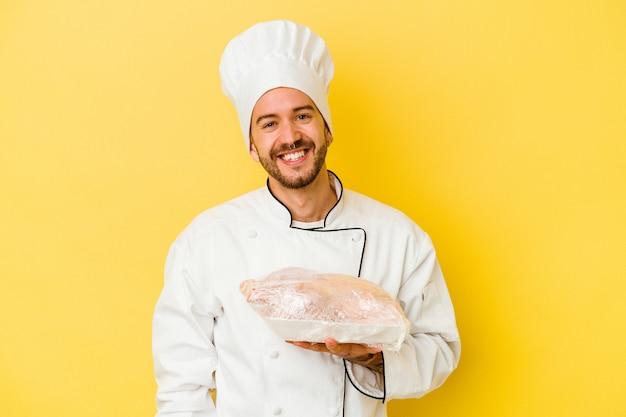 Pollo della holding dell'uomo giovane chef caucasico isolato su sfondo giallo felice, sorridente e allegro.