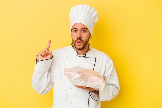 Uomo caucasico giovane del cuoco unico che tiene il pollo isolato su priorità bassa gialla che ha qualche grande idea, concetto di creatività.
