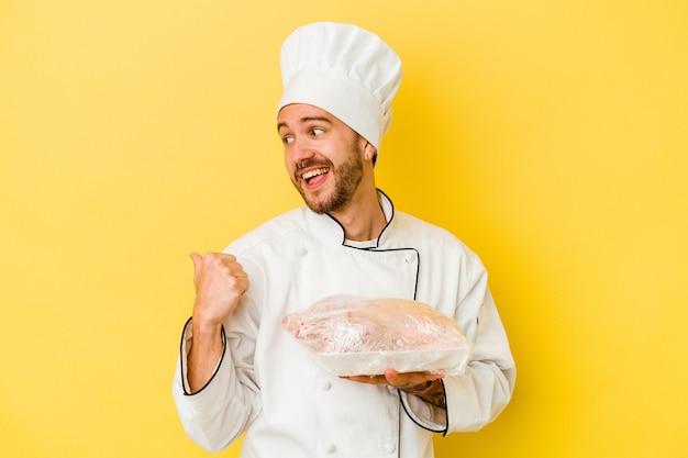 Il giovane uomo caucasico del cuoco unico che tiene il pollo isolato sui punti gialli del fondo con il dito del pollice via, ridendo e spensierato.