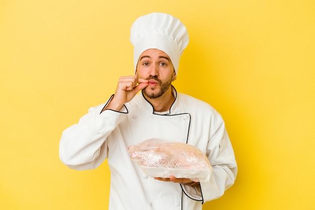 Uomo caucasico giovane del cuoco unico che tiene il pollo isolato su priorità bassa gialla con le dita sulle labbra che mantengono un segreto.