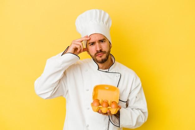 Uomo caucasico giovane del cuoco unico che tiene le uova isolate su fondo giallo che è scioccato, ha ricordato l'incontro importante