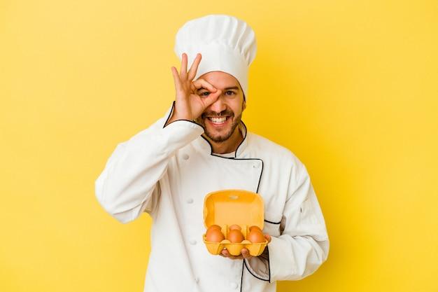 Il giovane uomo caucasico del cuoco unico che tiene le uova isolate su fondo giallo eccitato mantenendo il gesto giusto sull'occhio.