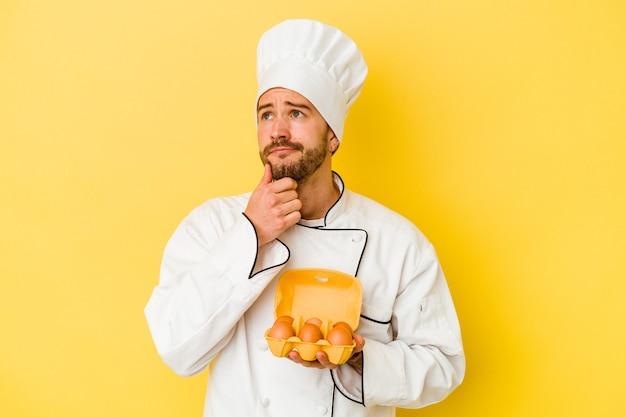 Uomo caucasico giovane del cuoco unico che tiene le uova isolate su fondo giallo che osserva obliquamente con espressione dubbiosa e scettica.