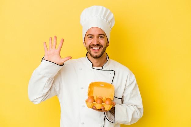 Uomo caucasico giovane del cuoco unico che tiene le uova isolate su sfondo giallo sorridente allegro che mostra il numero cinque con le dita.