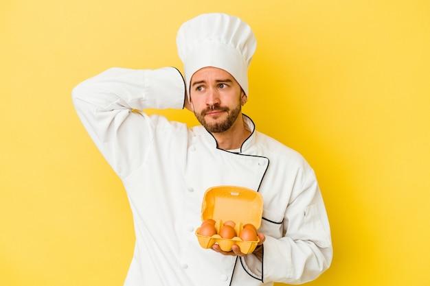 Uomo caucasico giovane del cuoco unico che tiene le uova isolate su fondo giallo che tocca la parte posteriore della testa, pensando e facendo una scelta.