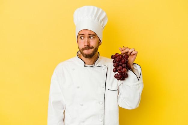 Il giovane uomo caucasico del cuoco unico che tiene l'uva isolata su priorità bassa gialla confusa, si sente dubbioso e insicuro.