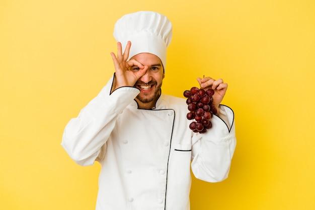 Il giovane uomo caucasico del cuoco unico che tiene l'uva isolata su priorità bassa gialla ha eccitato mantenendo il gesto giusto sull'occhio.