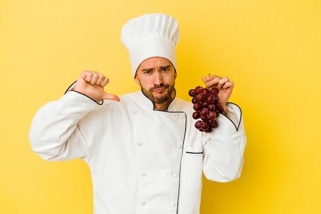 Il giovane uomo caucasico del cuoco unico che tiene l'uva isolata su priorità bassa gialla si sente orgoglioso e sicuro di sé, esempio da seguire.