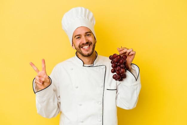 Uomo caucasico giovane del cuoco unico che tiene l'uva isolata su priorità bassa gialla gioiosa e spensierata che mostra un simbolo di pace con le dita.