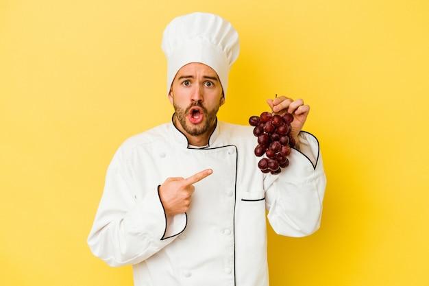Uomo caucasico giovane del cuoco unico che tiene l'uva isolata su fondo giallo che indica al lato