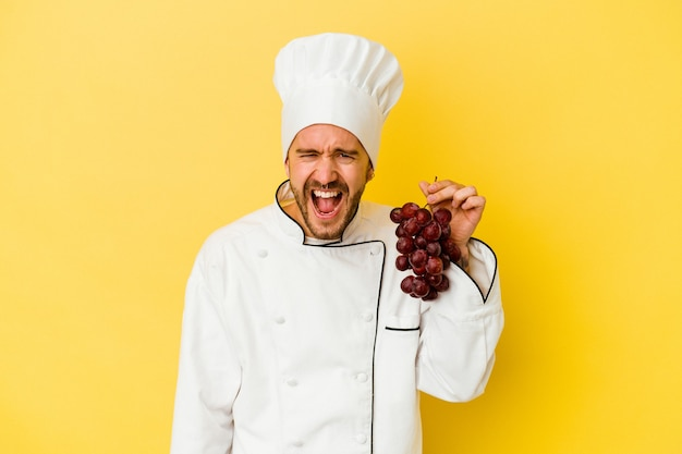 Uomo caucasico giovane del cuoco unico che tiene l'uva isolata su fondo giallo che grida molto arrabbiato e aggressivo