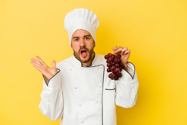 Uomo caucasico giovane del cuoco unico che tiene l'uva isolata su fondo giallo sorpreso e scioccato.
