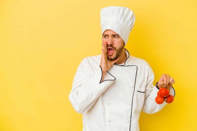 Il giovane uomo caucasico del cuoco unico che tiene i pomodori isolati su fondo giallo sta dicendo una notizia di frenata calda segreta e sta guardando da parte