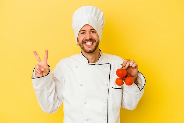 Uomo caucasico giovane del cuoco unico che tiene i pomodori isolati su priorità bassa gialla gioiosa e spensierata che mostra un simbolo di pace con le dita.