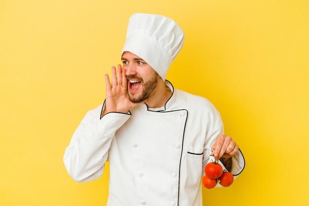 Uomo caucasico giovane del cuoco unico che tiene i pomodori isolati su fondo giallo che grida e che tiene il palmo vicino alla bocca aperta.