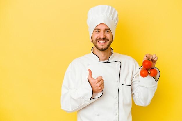 Uomo caucasico giovane del cuoco unico che tiene i pomodori isolati su fondo giallo che sorride e che alza il pollice in su