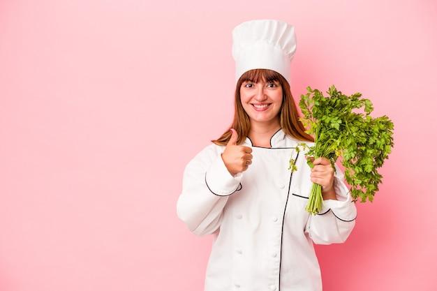 Giovane chef caucasico che tiene in mano il prezzemolo isolato su sfondo rosa sorridendo e alzando il pollice