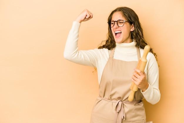 Giovane donna caucasica del cuoco unico che alza il pugno dopo una vittoria, concetto del vincitore.