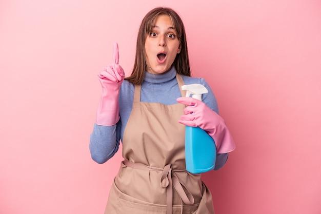 Giovane donna caucasica più pulita che tiene spray isolato su sfondo rosa con qualche grande idea, concetto di creatività.