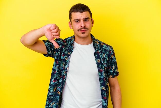 Giovane uomo caucasico cool isolato su sfondo giallo che mostra un gesto di avversione, pollice in giù. concetto di disaccordo.