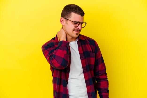 Giovane uomo caucasico cool isolato sulla parete gialla che ha un dolore al collo a causa dello stress, massaggiandolo e toccandolo con la mano.